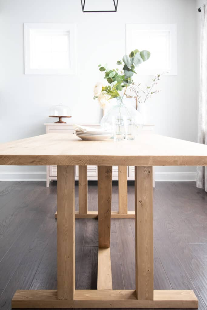 side view of DIY dining table made of 2x4s. Pine boards stained with Minwax Driftwood stain