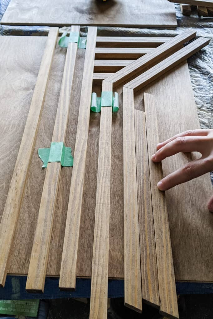 gluing wood trim pieces to plywood backing to create geometric pattern