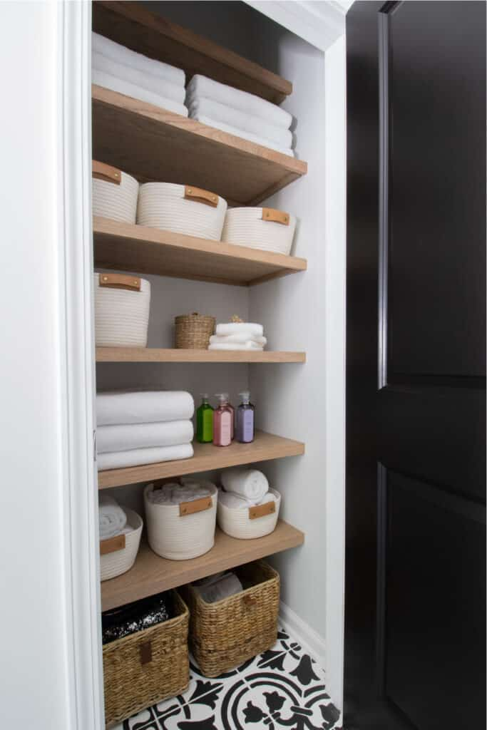 angled view of organized linen closet with light oak plywood shelving