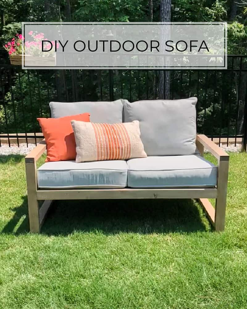 DIY outdoor sofa in grass with gray cushions and coral pillows