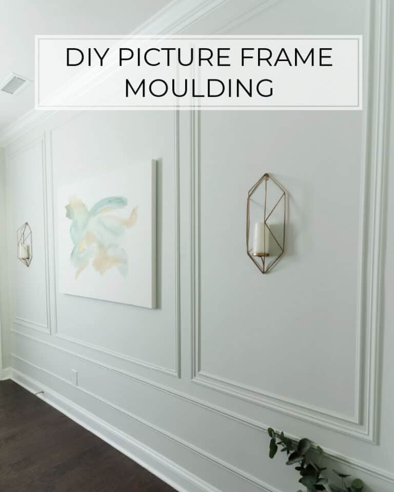 DIY picture frame moulding on light gray walls in entryway