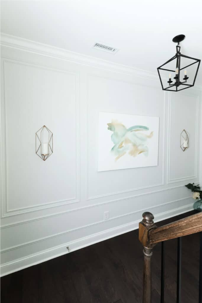 modern picture frame moulding with abstract art and candle sconces in entryway