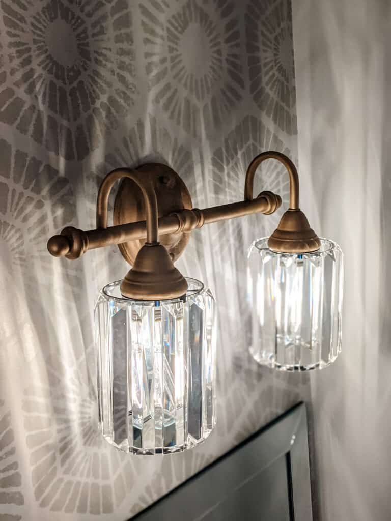 gold painted light fixture with glass shades hanging in bathroom